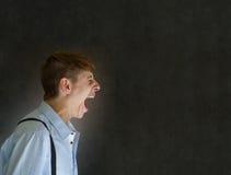 呼喊在黑板背景的恼怒的大嘴人 库存照片