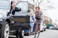 呼喊年轻的自行车骑士,当偏向为避免危险碰撞时 库存照片