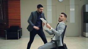 呼喊快乐的男性的办公室工作者有乐趣骑马椅子在大厅和投掷的文件谈话和 青年时期 影视素材