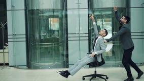 呼喊愉快的人的慢动作获得乐趣在办公室大厅骑马辗压椅子和投掷纸的衣服的和 股票视频