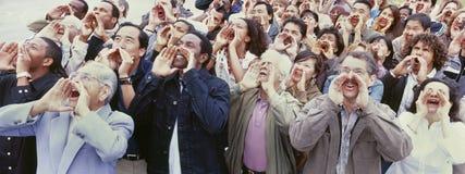 呼喊用在面孔的手的人群全景射击 免版税库存照片