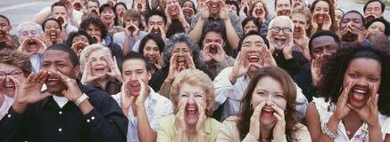 呼喊用在面孔的手的人群全景射击 库存图片