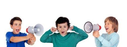 呼喊通过扩音机的滑稽的孩子对他的朋友 免版税库存图片