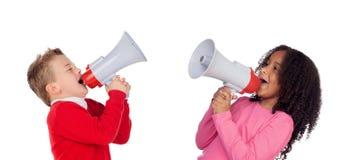 呼喊通过扩音机的滑稽的小男孩对他的朋友 免版税库存图片