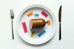 命名食品添加剂和香肠在板材的五颜六色的纸笔记有叉子的和刀子、食品添加剂和不健康的食物概念 免版税图库摄影