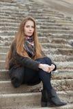 年轻和俏丽的妇女生活方式画象有摆在坐具体楼梯的华美的长的头发的调查照相机 免版税库存图片