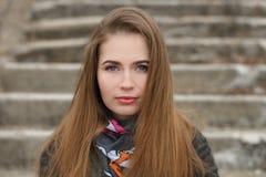 年轻和俏丽的妇女生活方式画象有摆在有浅景深的城市公园的华美的长的头发的concret 免版税库存照片