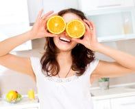 妇女用在眼睛的桔子 图库摄影