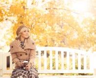 年轻和可爱的女孩坐一条长凳在秋天公园 免版税库存图片