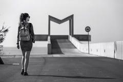 年轻和可爱的妇女沿道路走开在都市公园 免版税库存照片