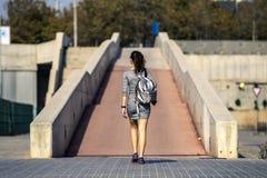 年轻和可爱的妇女沿道路走开在都市公园 库存照片