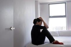 和哭泣坐床的沮丧的成人受害者妇女 免版税库存图片