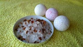 浴和大腌制槽用食盐的三颗相当小的炸弹与在毛巾的花瓣 库存照片