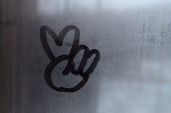 和平标志的图象画与一个misted玻璃窗的表面上的一个手指 两个手指的组合 库存图片
