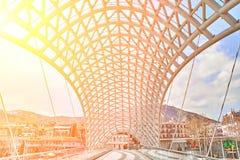 和平桥梁是在库那河的步行桥在第比利斯,乔治亚的首都 太阳火光 免版税图库摄影