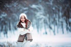 年轻和性感的女孩佩带的围巾和帽子在冬天礼服在白色 图库摄影