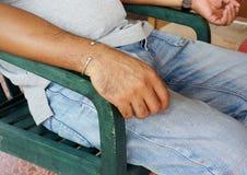 和投入手的中年人坐椅子 免版税库存照片