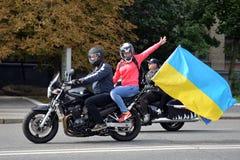 和挥动坐摩托车的女孩 免版税图库摄影