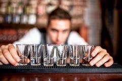 和排行小玻璃的侍酒者为酒精饮料做准备 免版税库存照片