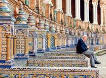 和放松坐著名Plaza de西班牙,安大路西亚的建筑学的例子长凳的年长人  图库摄影