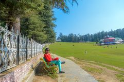 和放松坐高尔夫球场的夫人 免版税图库摄影
