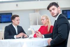 年轻和有动机的商人画象与他的队的 免版税库存图片