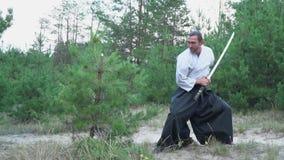 和服的一个人在有katana打击的森林砍一棵树,推它回到刀子并且做一点弓 股票视频