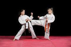 和服的两个女孩训练被配对的锻炼空手道 库存照片