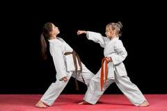和服的两个女孩训练被配对的锻炼空手道 图库摄影