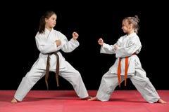 和服的两个女孩训练被配对的锻炼空手道 库存图片