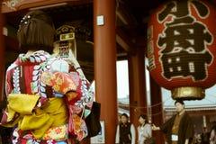 和服的女孩拍摄她的男朋友的在Senso籍寺庙入口在浅草,东京,日本 免版税图库摄影