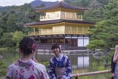 和服的妇女在金黄寺庙亭子前面 免版税库存图片