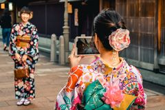 和服的日本女孩为照相的在一个手机在今池老镇 免版税库存照片