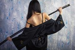 和服的美丽的亚裔女孩有katana的 免版税库存图片