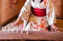 和服礼服的妇女演奏十三弦琴,日本竖琴 免版税库存照片
