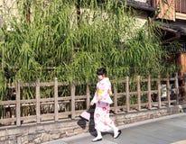 和服礼服的妇女走在与木篱芭的走道和背景竹树的 免版税库存照片