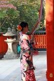 和服礼服立场的日本女孩和抓住对敲响响铃的织品绳索为保佑在Fushimi Inari寺庙 免版税库存照片
