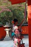 和服礼服立场的日本女孩和抓住对敲响响铃的织品绳索为保佑在Fushimi Inari寺庙 图库摄影