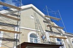 绘和涂灰泥外部议院脚手架墙壁 在外部整修期间,门面绝热和灰泥运作 免版税库存图片