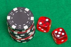 黑和红色纸牌筹码和模子在一床绿色毛毡 免版税图库摄影