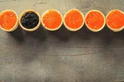 黑和红色鱼子酱果子馅饼框架,在灰色背景,顶视图的开胃菜点心,被定调子 库存照片