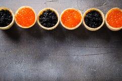 黑和红色鱼子酱果子馅饼框架,在灰色背景,顶视图的开胃菜点心 免版税库存图片