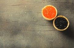 黑和红色鱼子酱果子馅饼,在灰色背景,顶视图的开胃菜点心,被定调子 库存图片