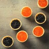 黑和红色鱼子酱果子馅饼,在灰色背景,顶视图的开胃菜点心,被定调子 图库摄影