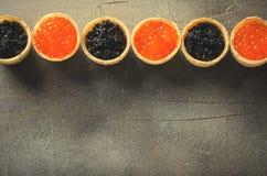 黑和红色鱼子酱果子馅饼,在灰色背景,顶视图的开胃菜点心 库存图片