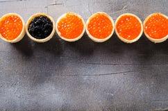 黑和红色鱼子酱果子馅饼,在灰色背景,顶视图的开胃菜点心 免版税图库摄影