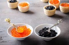 黑和红色鱼子酱果子馅饼,在白色碗的开胃菜点心 库存图片