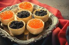 黑和红色鱼子酱果子馅饼,在银色盘子的开胃菜点心 库存图片