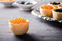 黑和红色鱼子酱果子馅饼,在银色盘子的开胃菜点心 图库摄影