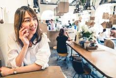 年轻和美丽的亚裔妇女谈话在手机在咖啡店、通信或者咖啡馆偶然生活方式概念 库存照片